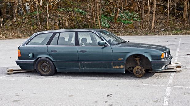Blå skrotbil utan hjul uppställd på parkeringsplats_740x413