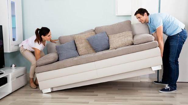 Par som bär in en stor vit soffa i sitt vardagsrum.