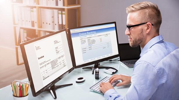 Person som betalar e-faktura via bank på dator.