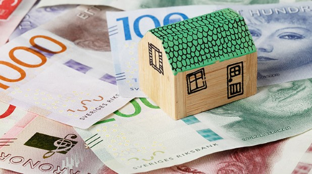 Modell av ett hus placerat ovanpå svenska sedlar