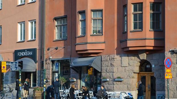 Bostadshus på gata med uteservering. lgh-stockholm_asa-larsson_740x413