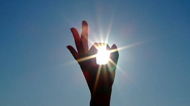 Hand med solstrålar
