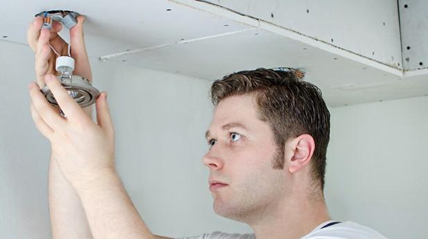 6881552-certified-electrician-installing-light-bulb