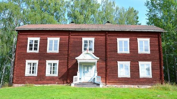 kulturvarde_tvåvånings gammal gård i rött timmer, vita fönsteromfattningar,_mostphotos