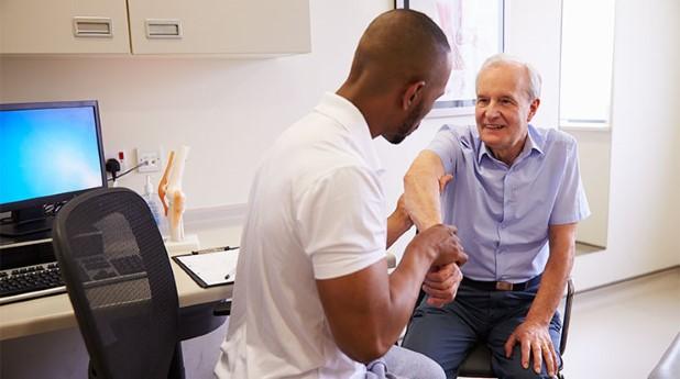 Läkare som undersöker patient. Arbetsrelaterade sjukskrivningar ökar, vanligast är felbelastningar.