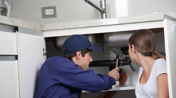 Två personer arbetar med rördragning under diskbänk.