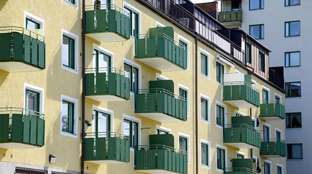 Gult hyreshus med gräöna balkongfronter. Utvecklad modell för hyressättning vid nyproduktion.