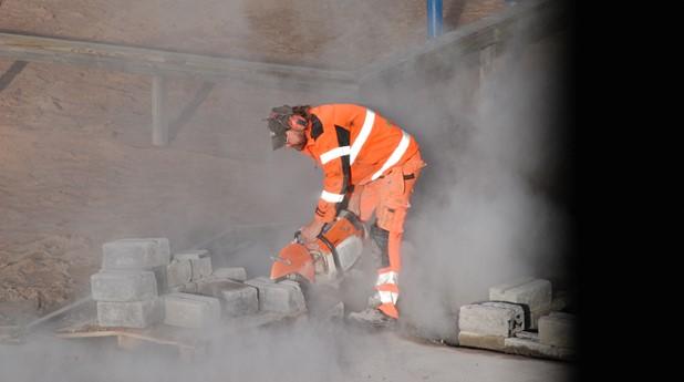 Man i oranga arbetskläder som kapar betong och kvartsdamm uppstår, Rolf Karlsson