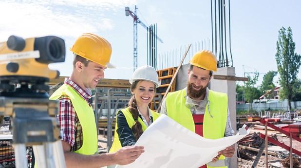 En kvinna och två män på en byggarbetsplats
