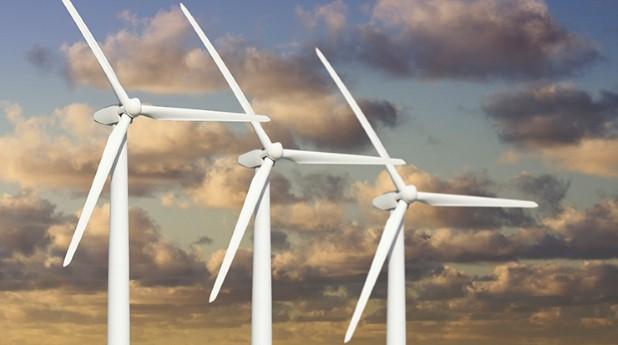 Tre vindkraftverk över dramatiska moln