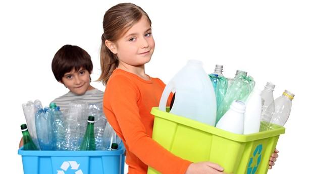 Barn som bär på plastbackar med flaskor som ska återvinnas