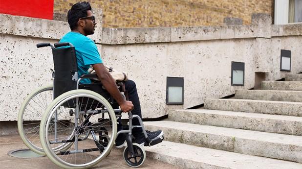 Man i rulstol framför en trappa