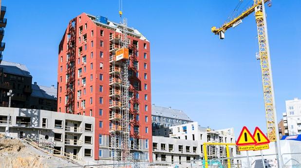 Flerfamiljshus i rött tegel under produktion. Trygg-bostadsrattsforening