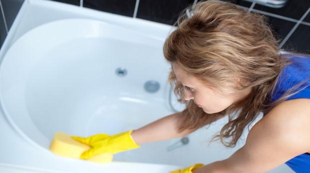 Kvinna som gör rent badkar