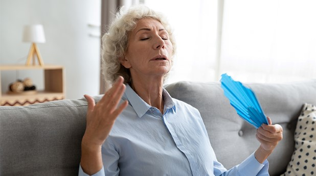 35563458-tired-older-woman-waving-fan-suffering-from-heat-at-home