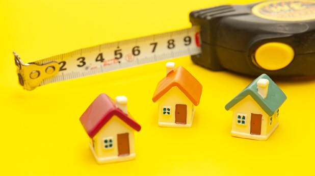 38513614-building-tape-measure-and-miniature-houses-on-a-yellow