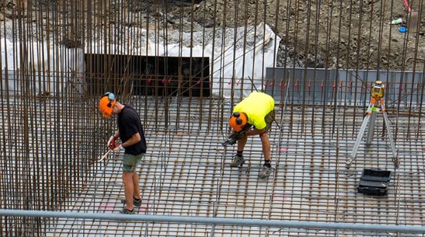Två personer armerar bostadskonstruktion