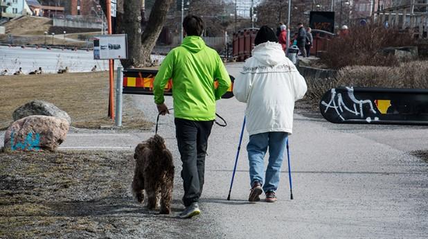 Två personer som är ute och promenerar med en hund