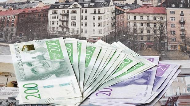 Ett antal sedlar framför vy av bostadshus_hans-christiansson