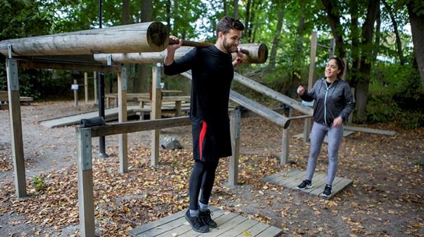 två personer tränar på utegym