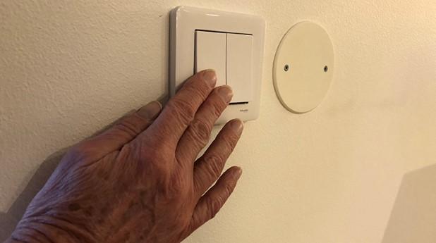 Hand som trycker på strömbrytare för att släcka belysning.