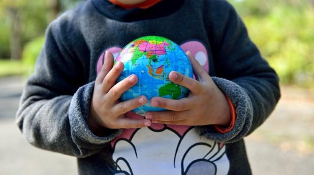 Barnhänder som håller i en jordglob