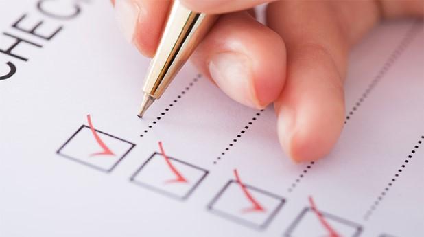 9803935-businesswoman-writing-on-checklist