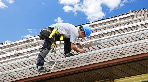 1809359-man-working-on-roof-installing-rails-for-solar-panels
